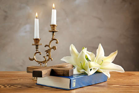 Wooden cross, Holy Bible and white lily on table