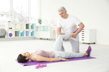 Young disabled woman with senior orthopedist in rehabilitation clinic Stock Photo