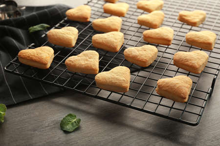 Baking grid with heart shaped butter cookies on table