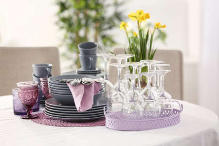 Set of dishware with lilac accessories on table in restaurant