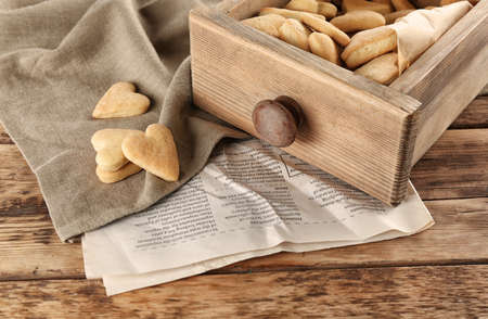 Wooden drawer with heart shaped butter cookies on table