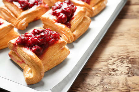 Tray with delicious puff pastries and cherry on wooden table