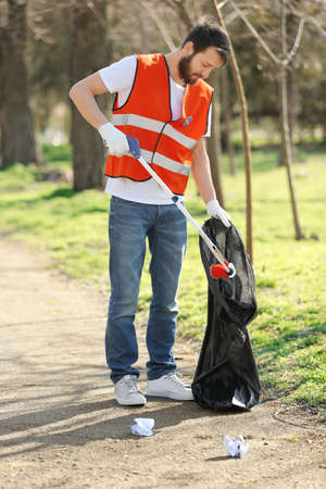 Young volunteer picking up litter in park Stock Photo