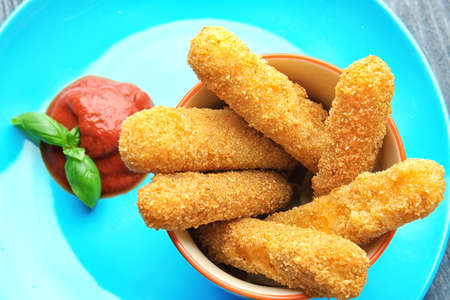 Cheese sticks in bowl and tomato sauce on plate