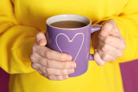 Woman holding beautiful lilac color cup, closeup