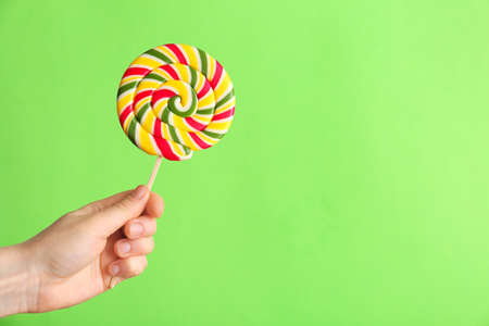 Female hand with tasty lollipop on color background