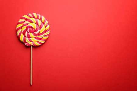 Tasty lollipop on color background