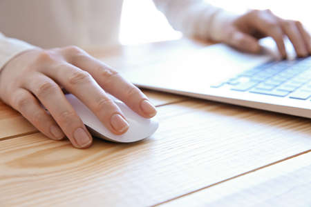 Woman using computer mouse with laptop on wooden table