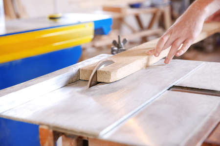 Carpenter sawing timber in workshop