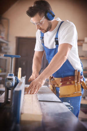 Carpenter working with timber in shop