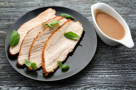 Plate with delicious sliced turkey and gravy boat on wooden table Stock Photo