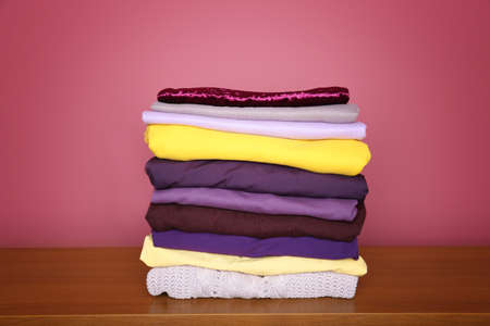 Stack of clothes on wooden table. Combination of lilac and yellow colors