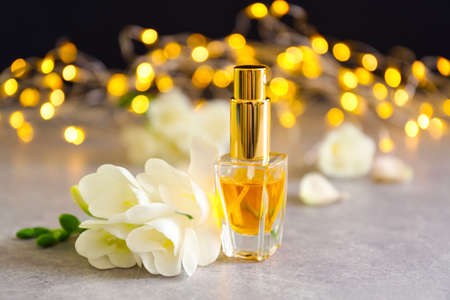 Perfume bottle and flowers on blurred background
