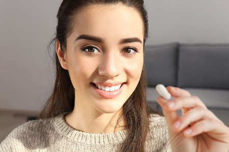 Beautiful young woman with pill at home, closeup
