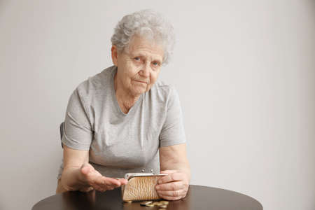 Senior woman counting coins while sitting at table. Poverty concept Foto de archivo
