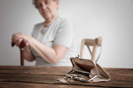 Purse with coins and blurred senior woman on background. Poverty concept