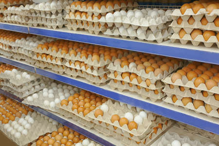 Cardboard trays with chicken eggs on shelves at supermarket Standard-Bild - 97775181