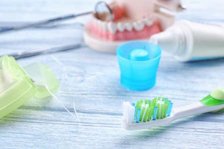 Cepillo de dientes y seda dental sobre fondo de madera, primer plano% 00
