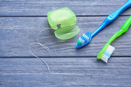 Toothbrushes and dental floss on wooden background Фото со стока