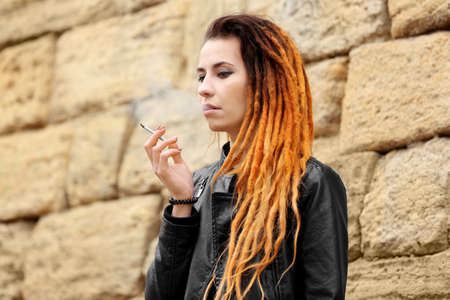 Young beautiful woman smoking weed on stone background
