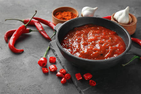 Composition with tasty chili sauce on grey textured table