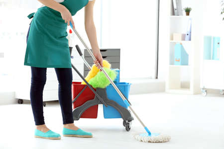 Woman washing floor in office. Cleaning service concept