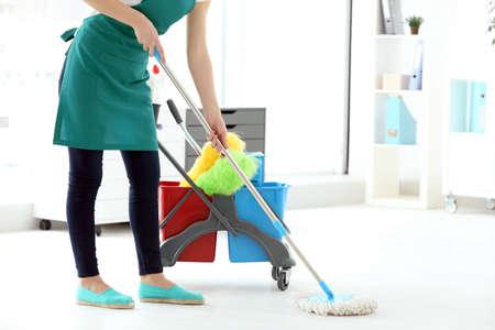 De wasvloer van de vrouw in bureau. Schoonmaak service concept