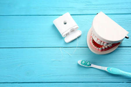 Cepillo de dientes, hilo dental y maqueta de mandíbula de plástico sobre fondo de madera de color Foto de archivo
