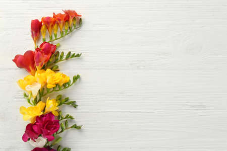 Beautiful freesia flowers on light wooden background