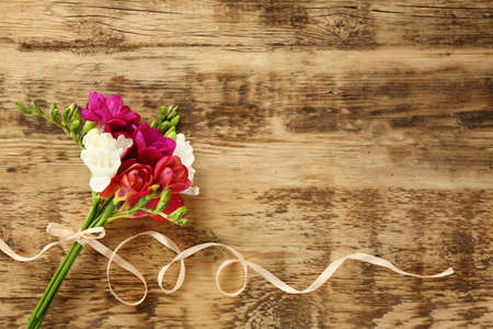 Bouquet of beautiful freesia flowers on wooden background
