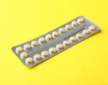 Birth pills on yellow background Foto de archivo - 97770873