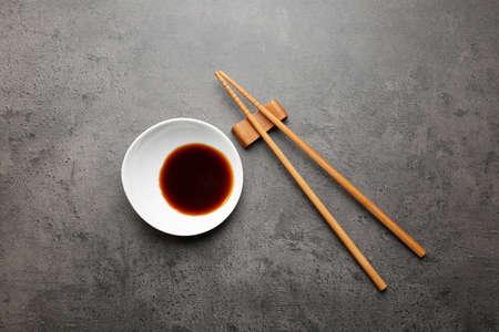 Composizione con gustosa salsa di soia su sfondo grigio con texture% 00