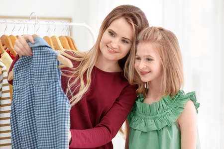 Mother and daughter choosing clothes in modern shop