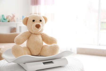 Baby scales with teddy bear on table in room