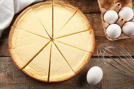 Tasty homemade cheesecake, eggs and whisk on wooden table Stock Photo