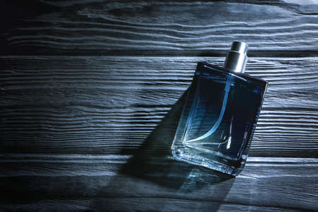 Bottle of modern male perfume on dark wooden background