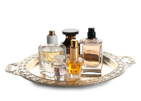 Metal tray with bottles of perfume on white background