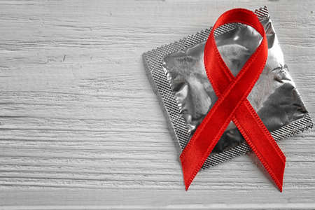 Condom and red ribbon on wooden background. Safe sex concept Foto de archivo - 97754566