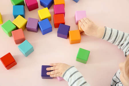Cute little child playing with colorful cubes at home