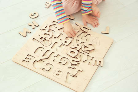Cute little child playing with letters while sitting on floor at home