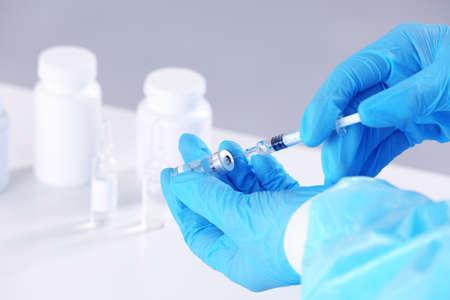 Manos de médico con jeringa y medicina en la clínica, primer plano