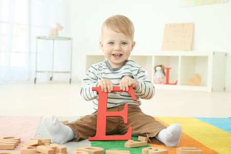 Cute little child with letter E sitting on floor at home