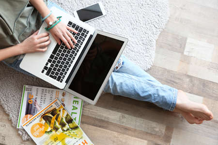 Young girl sitting on rug and using laptop at home