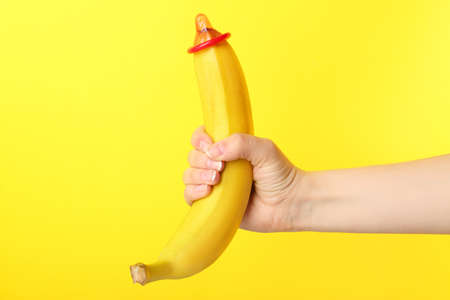 Woman holding banana with condom against color background. Safe concept
