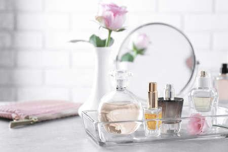 Vassoio di vetro con bottiglie di profumo sul tavolo