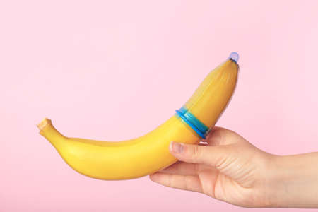 Woman holding banana with condom against color background. Safe sex concept