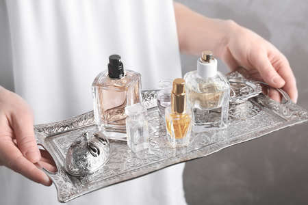 Woman holding metal tray with bottles of perfume