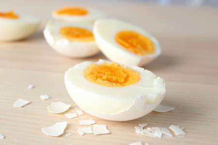 Sliced hard boiled eggs in shell on wooden surface. Nutrition concept