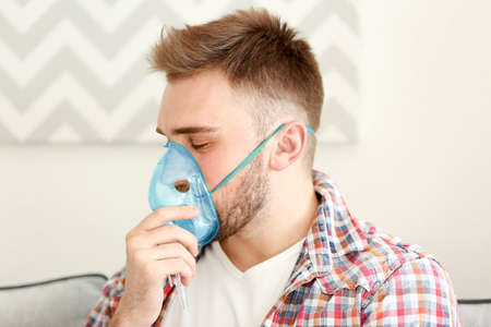Young man using nebulizer for asthma and respiratory diseases at home Stock Photo