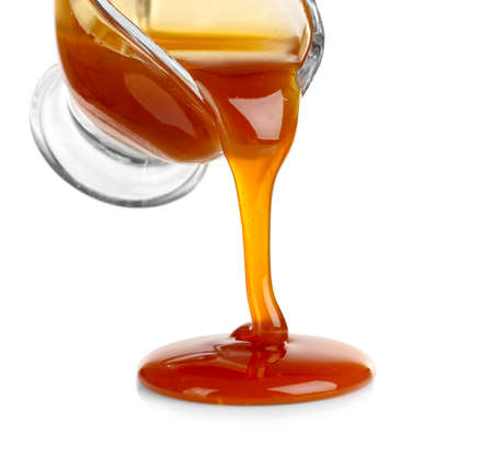 Pouring caramel sauce onto white background
